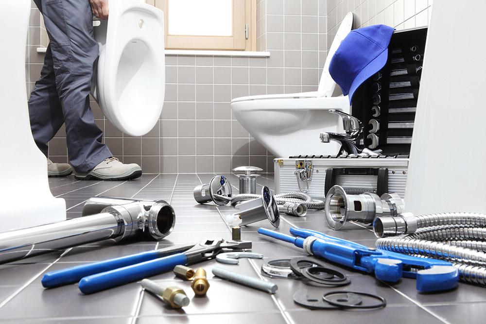 plumber at work in a bathroom, plumbing repair service